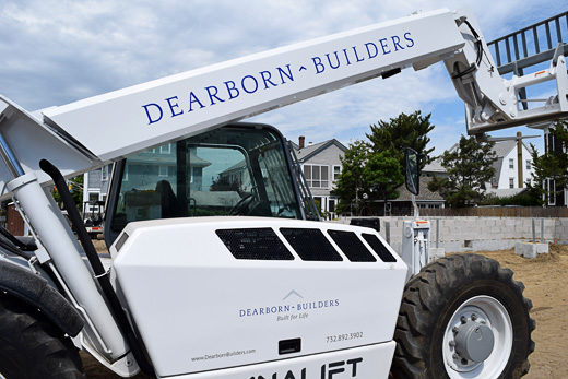 Boom loader with Dearborn Builders logo